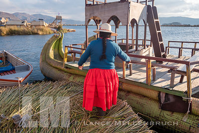 "Uros resident leading tourists to a boat called the ""Mercedes"" for a tour of the Uros floating islands"