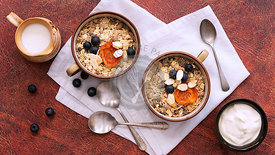 Breakfast setting, two servings of natural bircher muesli with dried apricots; blueberries and slithered almonds, a jug of mi...