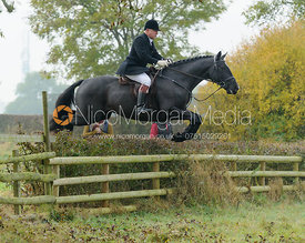 James Mossman jumping a hedge near Wilson's - The Cottesmore at Langham.