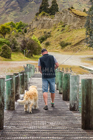 man walking on a jetty after fishing with his dog