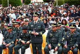 Army officer holding candle during central mass for the Virgen de la Candelaria festival, Puno, Peru