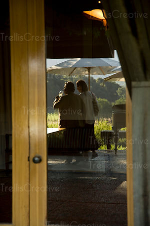 Reflection of a couple drinking wine on a patio