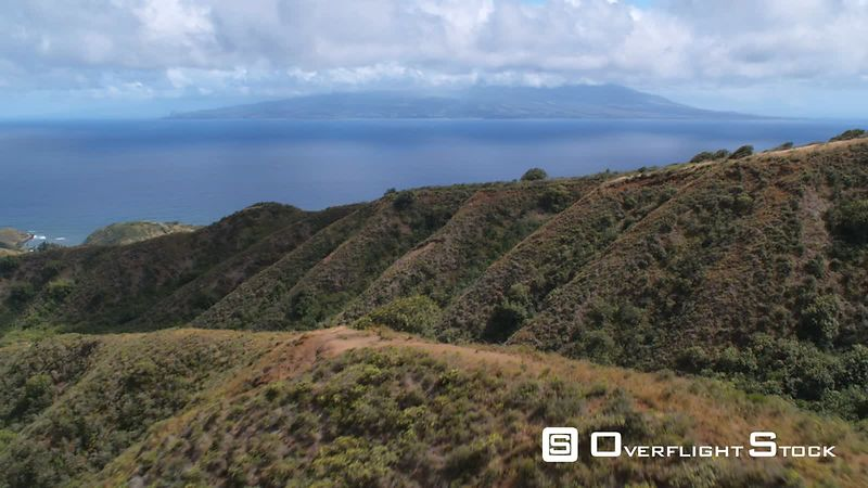 Over forested hills and ridges on Molokai with Maui in the distance.