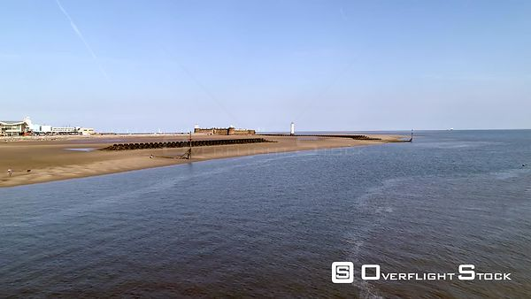 Drone flies towards New Brighton Beach, Fort Perch and Lighthouse on a summer's morning