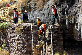 Man ties rope to one of the new foundation ropes so it can be pulled across the canyon , Q'eswachaka , Canas province , Peru