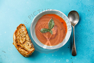 Gazpacho Tomato summer soup and bread on blue background