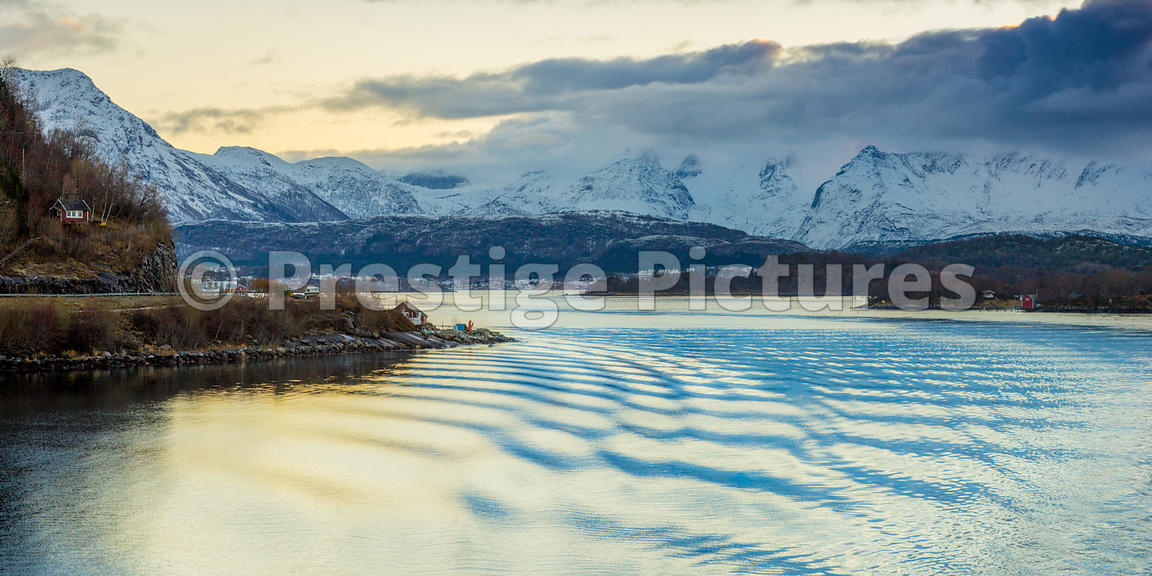 Panorama or Snow covered Mountains and an orange glistening sea