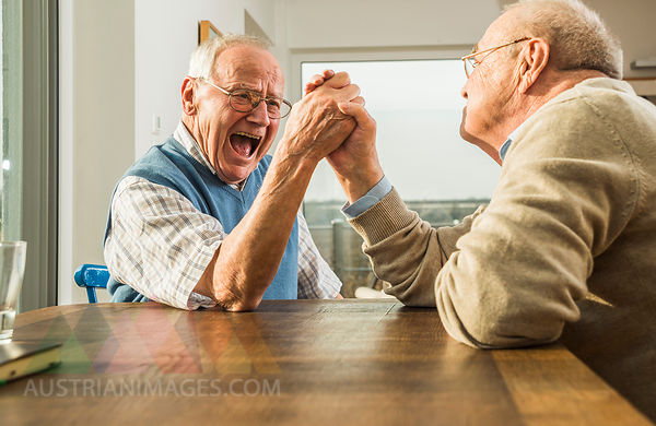Two senior friends arm wrestling