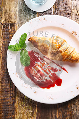 Pastry served with ice cream scoop drizzled with sauce
