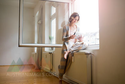 Mature woman in empty room using tablet at the window
