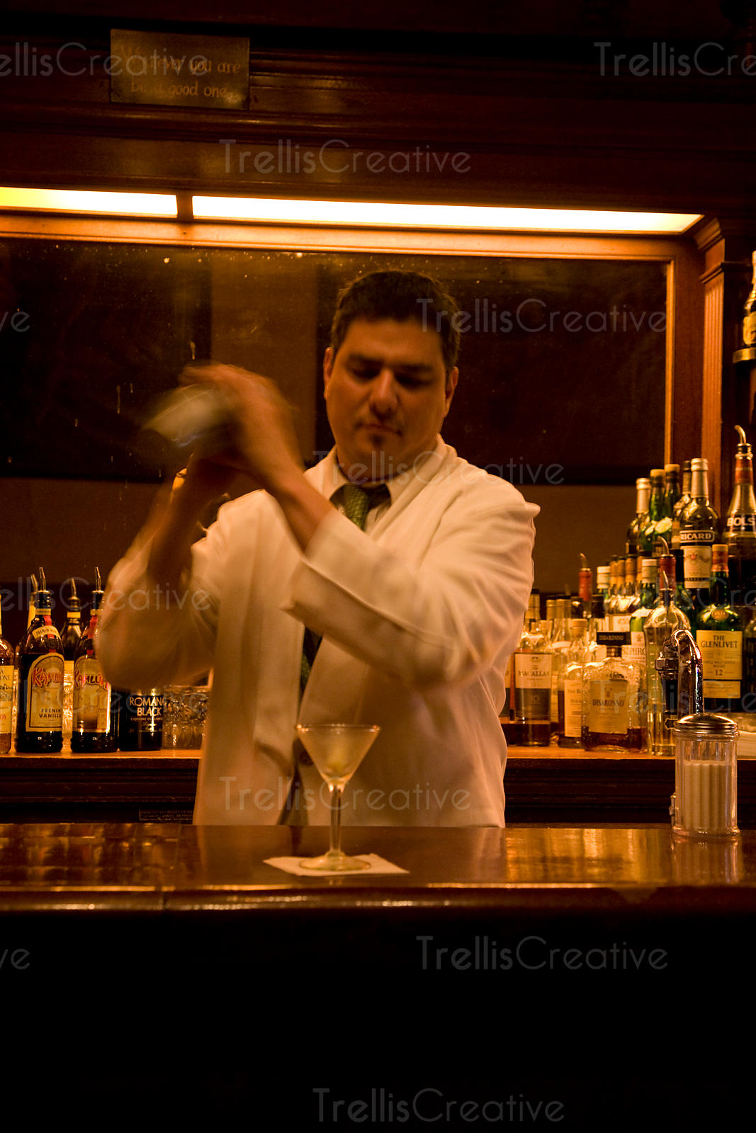 Bartender shakes a martini shaker before pouring cocktail