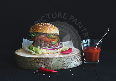 Fresh homemade burger on wooden serving board with spicy tomato sauce, sea salt and herbs over black  background.