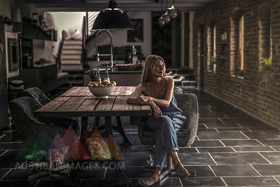 Woman sitting at dining table in her country house, thinking