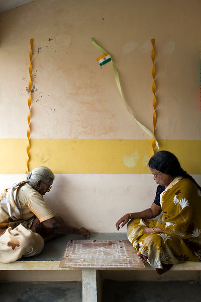 India - Cuddalore - Two elders play a board game outside their cottage