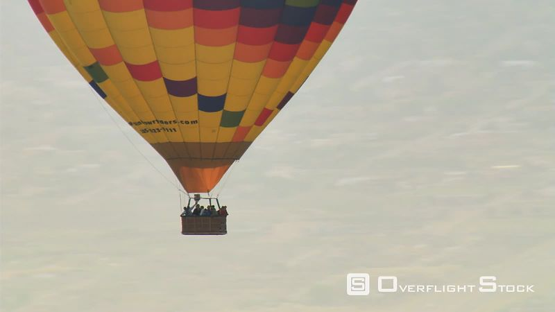 Close mid-air view of hot air balloon and passengers in basket.