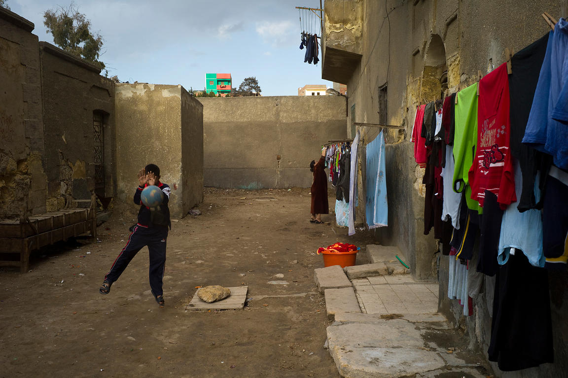 Egypt - Cairo - Boys play football in the street whilst a woman hangs washing on a line to dry in the Northern cemetery area ...