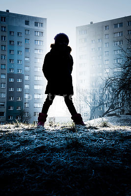 The silhouette of a little girl in a coat standing outside in the cold in front of blocks of flats.