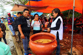 Woman serving chicha from large ceramic urn during carnival, Canasmoro, Tarija Department, Bolivia