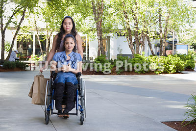 Young woman using a wheelchair shopping with family