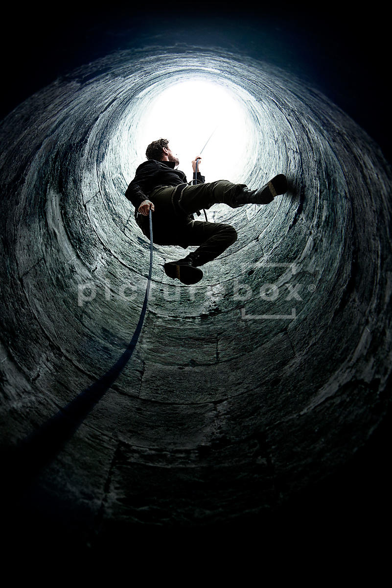 The silhouette of a men descending on a rope into a dark shaft/well.