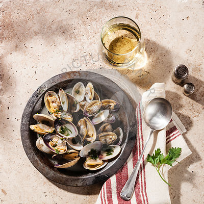 Shells vongole venus clams in metal dish and wine on stone background