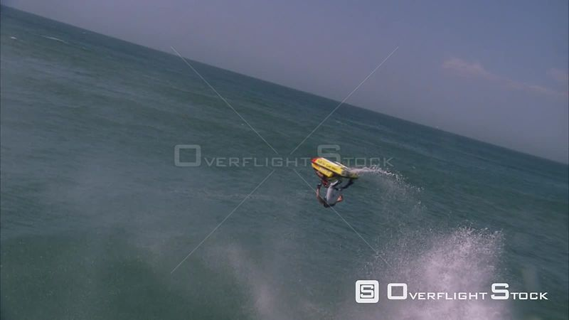 Slow motion shot of a jet skier ramping a wave, flipping horizontally in the air and splashes down. KwaZulu Natal South Africa