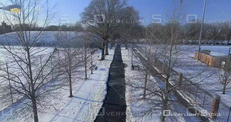 Aerial Rising Snow Covered Pathway and Fields Winter Day Brooklyn Prospect Park NYC