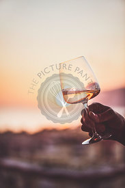 Rose wine in hand with sunset and sea at background