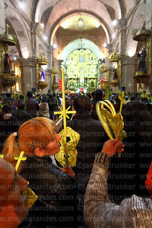 People holding crosses and ornaments made out of palm leaves inside San Francisco church during mass on Palm Sunday, La Paz, ...
