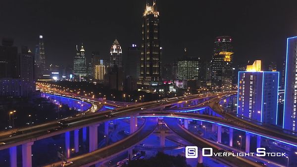 Elevated Road Overpass at Night with Blue Illumination and Shanghai Cityscape. China. Aerial View. Drone is Flying Backward a...