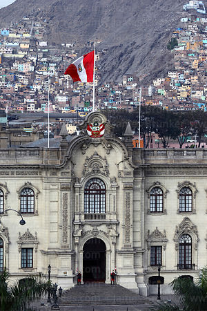 Facade of government palace, shanty town on side of Cerro San Cristobal in background, Lima, Peru