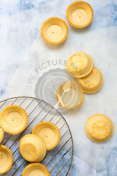 Small baked pastry tartlet cases cooling on a wire rack and baking paper.