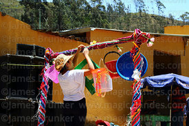 Woman hanging up prizes next to a wallunk'a / swing during Todos Santos festival, Morochata, Cochabamba Department, Bolivia