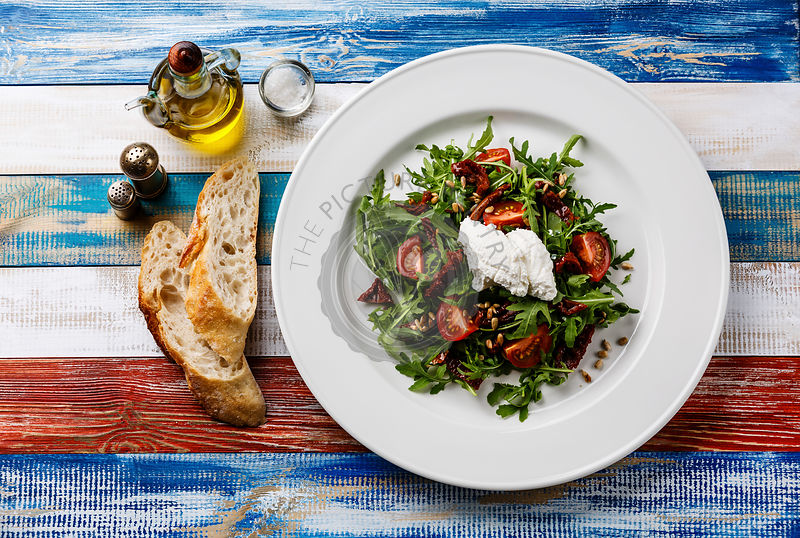 Salad with arugula, sun-dried tomatoes, sunflower seeds and ricotta cheese on white plate on wooden background