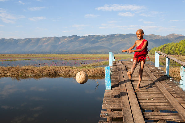 Nahosu, 8 ans, moine novice, frappe dans un ballon de football à partir d'une passerelle au dessus d'un canal du lac Inle, Birmanie / Nahosu, 8 years old, novice monk, strikes a football from a footbridge over an Inle Lake canal, Burma