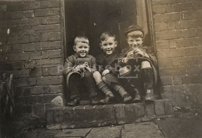 NOT FOR MISERY MEMOIR USAGE - An old family photograph of a three boys sitting on a doorstep, 1940's / 50's