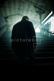 An atmospheric image of a mystery man walking up some steps at a European train station.