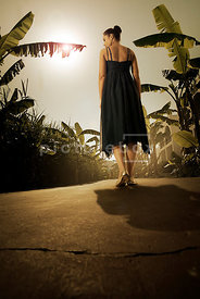 An atmospheric image of a mystery woman in a dress, walking down an empty, exotic path.