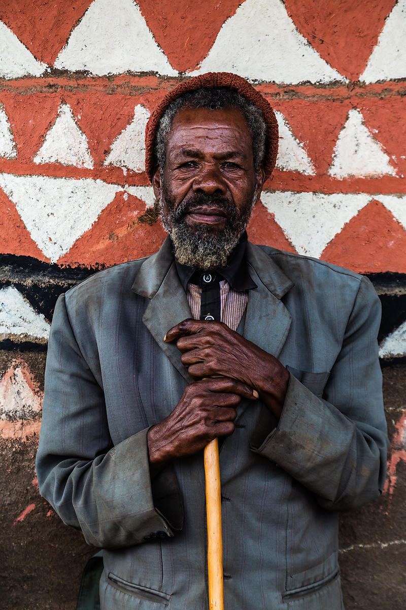 Portrait of an Elderly Man against Decorated Hut.