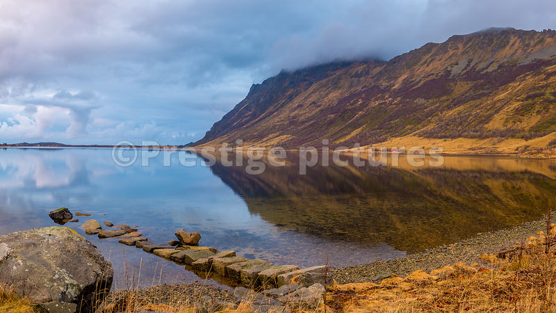 Ridge reflecting in the still waters of a fjord with a cloudy sky