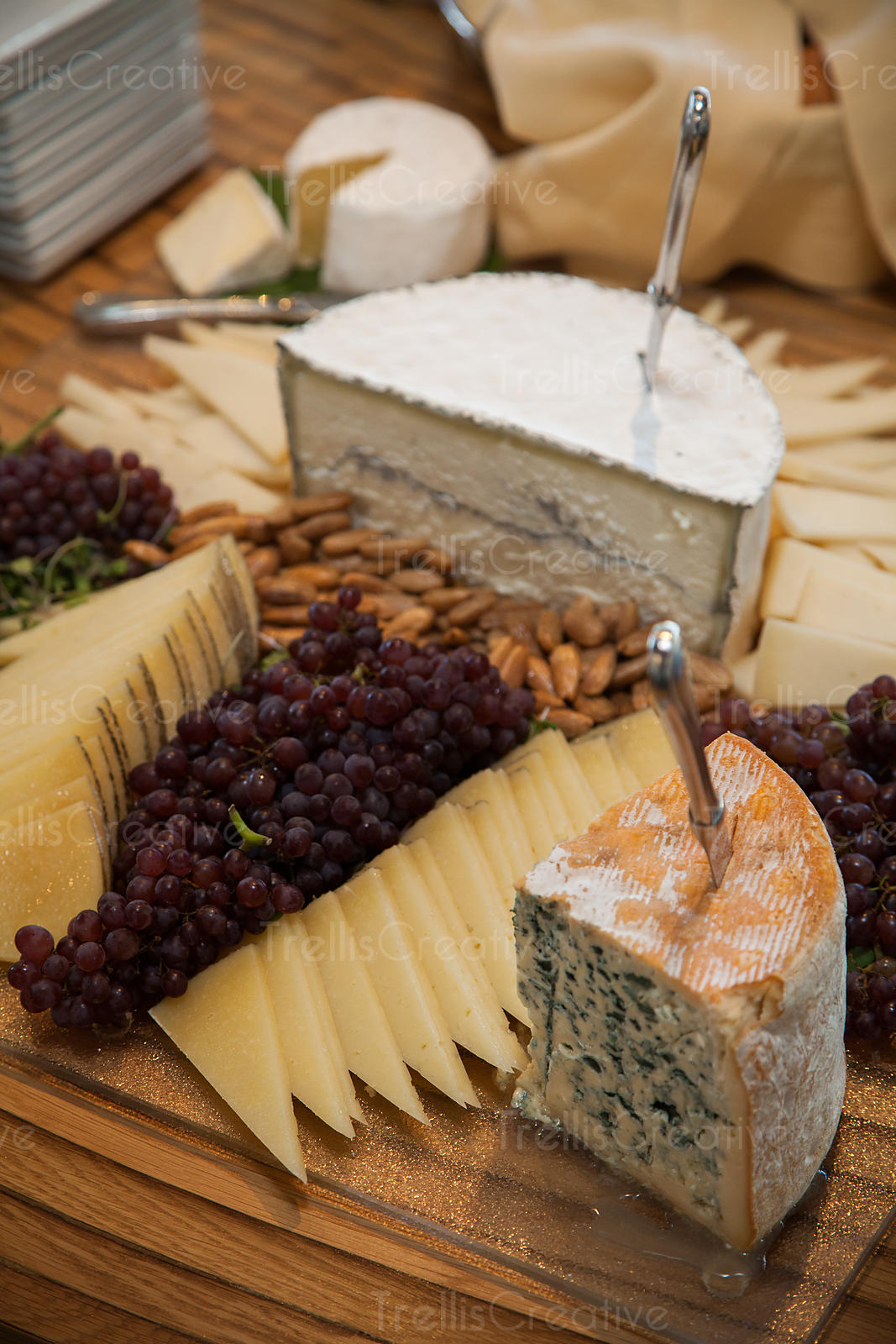 A variety of cheeses, nuts, and grapes artfully displayed