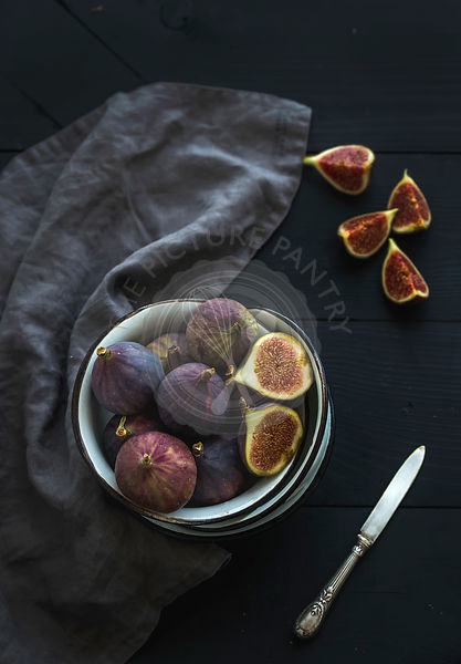 Rustic metal bowl of fresh figs on dark background, top view