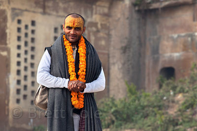 A Hindu adorned in marigold garlands, along the Ganges River near Scindia Ghat, Varanasi, India.