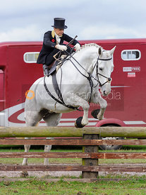 Amy Bryan-Dowell jumping a hunt jump behind the kennels