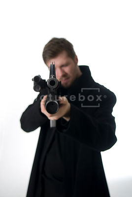 An image of a mystery man in a black coat, standing and pointing a gun.