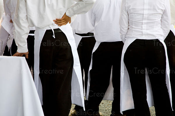 Waiters dressed in white shirts and black pants wait to serve