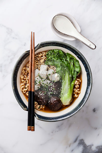 Miso Ramen Asian noodles with shiitake, tofu and pak choi cabbage in bowl on white marble background