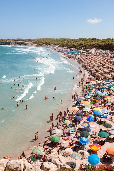 Beach crowded with tourists in summer, Salento, Apulia, Italy