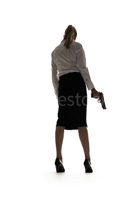 A semi-silhouette of a smartly dressed woman holding a gun – shot from low level.