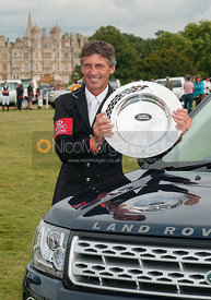 Andrew Nicholson poses with the Land Rover Trophy in front of Burghley House - prizegiving ceremony - Land Rover Burghley Hor...
